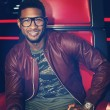 Usher wearing a pair of large, thick-frame glasses to support his last remaining contestant on NBC's The Voice.